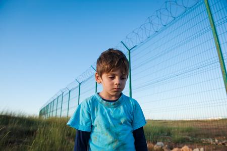 Foto de upset little boy refugee with dirty face near wall fence on border - Imagen libre de derechos