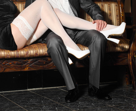 girl in white stockings seduces man indoors. Embrace the men and women in a restaurant.