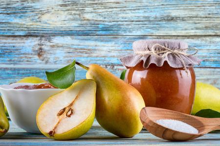 Foto de Glass jar of homemade pear jam with fresh fruits and ingredients on woody background - Imagen libre de derechos