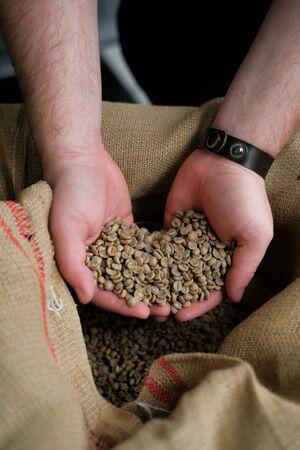 Foto de green unroasted coffee beans in hands on burlap background. - Imagen libre de derechos