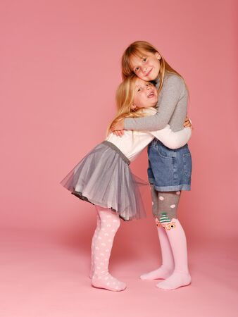 Photo pour Two cute little girls are standing next to each other on a pink background in the studio. Kindergarten, childhood, fun, family concept. Two fashionable sisters posing. - image libre de droit