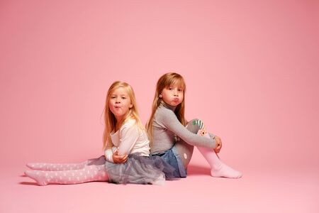 Photo pour Two cute little girls are sitting next to each other on a pink background in the studio. Kindergarten, childhood, fun, family concept. Two fashionable sisters posing. - image libre de droit