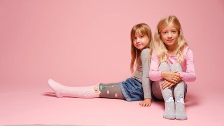 Foto de Two cute little girls are sitting next to each other on a pink background in the studio. Kindergarten, childhood, fun, family concept. Two fashionable sisters posing. - Imagen libre de derechos