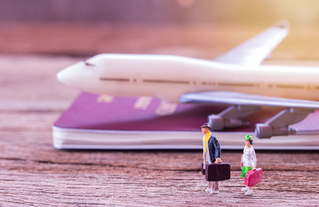 Photo pour Miniature people traveler standing on the floor and airplane,retro alarm clock,map,notebook on a wooden table. Photo in retro color image style. Top view with copy space for use.business and travel concept. - image libre de droit