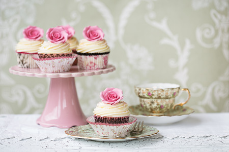 Photo pour Afternoon tea with rose cupcakes - image libre de droit