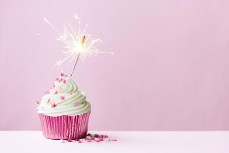 Photo pour Pink cupcake decorated with a sparkler - image libre de droit
