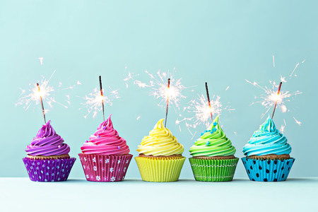 Photo pour Row of colorful cupcakes with sparklers - image libre de droit