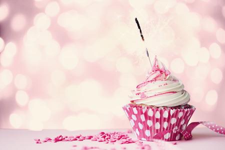 Photo pour Pink cupcake with sparkler and fairy lights - image libre de droit