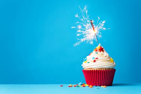 Foto de Cupcake with sparkler against a blue background - Imagen libre de derechos