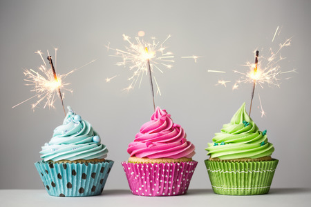 Foto de Row of three cupcakes with sparklers - Imagen libre de derechos