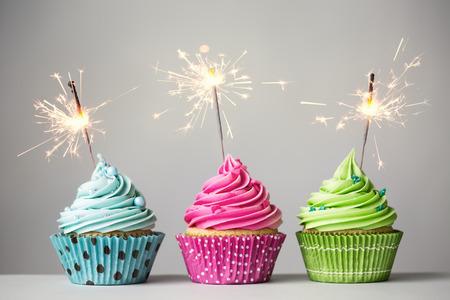 Photo pour Row of three cupcakes with sparklers - image libre de droit