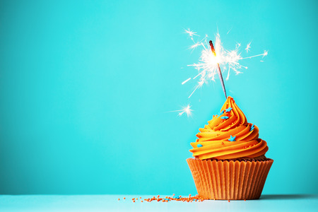 Photo for Orange cupcake with sparkler and copy space to side - Royalty Free Image