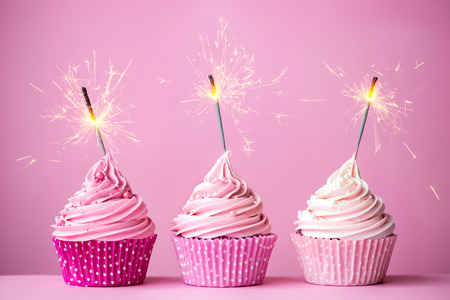 Photo pour Three cupcakes with pink frosting and sparklers - image libre de droit