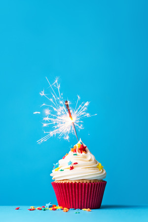 Photo for Cupcake with sparkler against a blue background - Royalty Free Image
