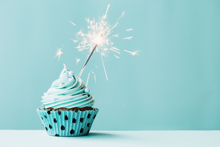Photo pour Cupcake with sparkler against blue - image libre de droit