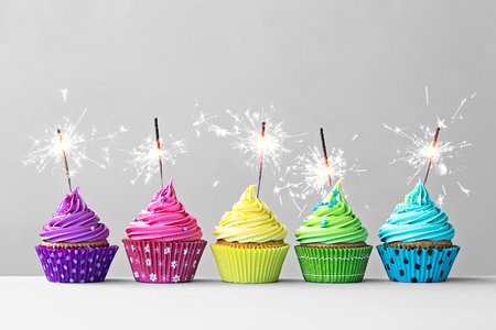 Foto de Row of colorful cupcakes with sparklers - Imagen libre de derechos