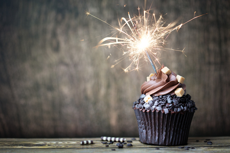 Photo pour Chocolate cupcake with a sparkler - image libre de droit