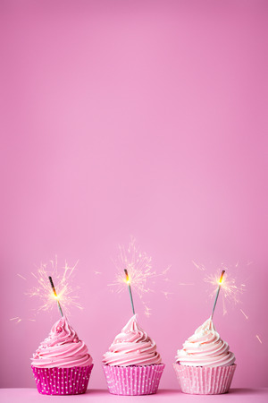 Photo for Pink cupcakes with sparklers and copy space above - Royalty Free Image