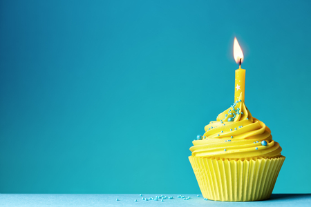 Photo for Yellow birthday cupcake on blue - Royalty Free Image