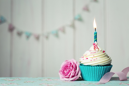 Photo pour Cupcake with single candle and pink rose - image libre de droit