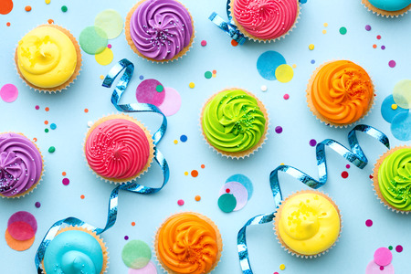 Foto de Colorful cupcake party background on blue - Imagen libre de derechos