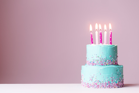Photo for Tiered birthday cake with pink candles - Royalty Free Image