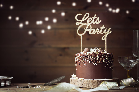 Photo pour Chocolate celebration cake in a party setting - image libre de droit
