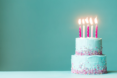 Foto de Tiered birthday cake with pink candles and sprinkles - Imagen libre de derechos
