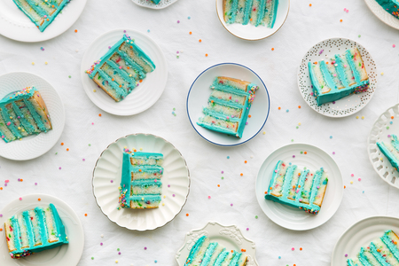 Photo for Slices of birthday layer cake overhead view - Royalty Free Image