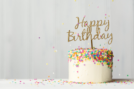 Photo pour Colorful birthday cake with golden happy birthday banner and falling sprinkles - image libre de droit