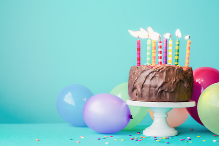 Photo for Chocolate birthday cake with colorful candles and balloons - Royalty Free Image