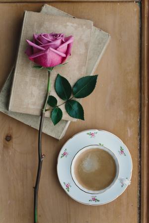 Foto de Coffee in a vintage teacup with a faded pink rose - Imagen libre de derechos