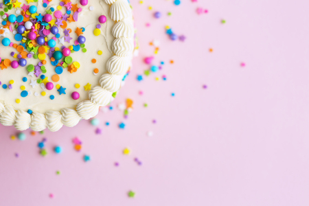Foto de Birthday cake with sprinkles on a pink background - Imagen libre de derechos