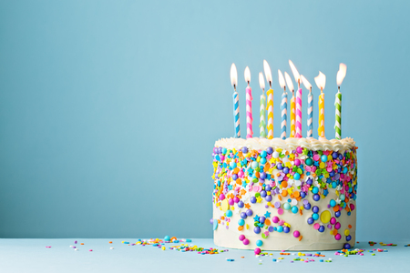 Photo for Colorful birthday cake with sprinkles and ten candles on a blue background with copyspace - Royalty Free Image
