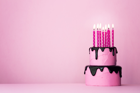 Photo for Pink tiered birthday cake with drip icing and lots of candles - Royalty Free Image