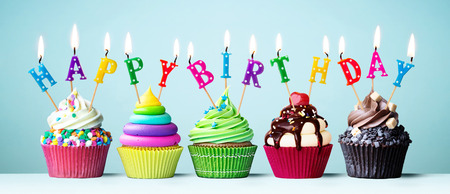 Photo for Colorful cupcakes with candles spelling Happy Birthday - Royalty Free Image