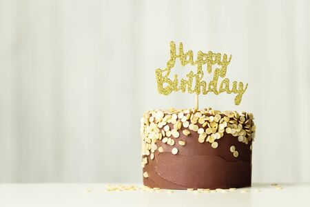 Foto de Chocolate birthday cake with golden happy birthday sign - Imagen libre de derechos