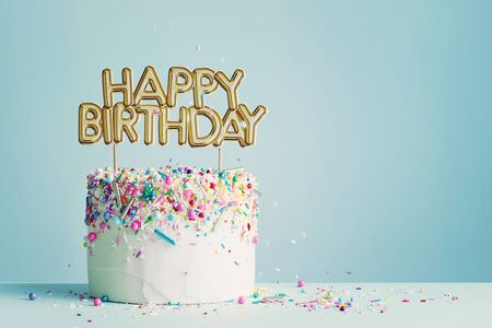 Photo pour Birthday cake with gold happy birthday banner - image libre de droit