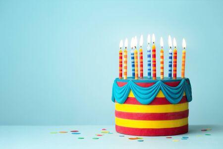 Foto de Brightly colored birthday cake with colorful candles - Imagen libre de derechos