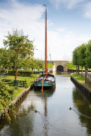 Foto de The boat at the canal in the traditional old fisherman village open-air museum of Zuiderzee (Zuiderzeemuseum), Enkhuizen, Netherlands. - Imagen libre de derechos