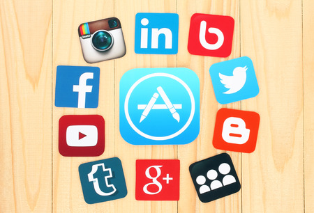 Photo pour KIEV, UKRAINE - JULY 01, 2015: Around AppStore icon are placed famous social media icons such as: Facebook, Twitter, Blogger, Linkedin and others, printed on paper and placed on wooden background. - image libre de droit