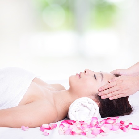 Beautiful asian woman enjoy receiving face and head massage at spa with nature green background