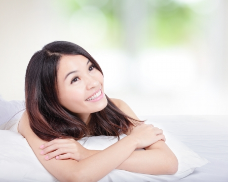 Photo for Charming woman Smile face close up and she lying on the bed in the morning with nature green background, model is a asian girl - Royalty Free Image