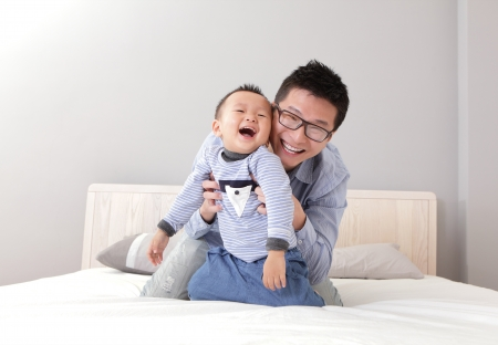 Photo for young father play with his son boy on the bed at home, asian lifestyle - Royalty Free Image