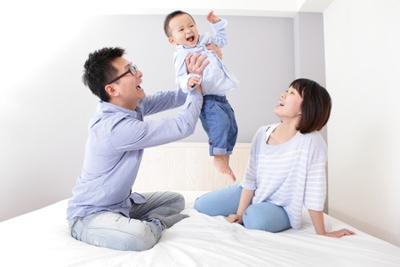 Photo for happy father hug his son with smile mother sitting on bed at home, asian family - Royalty Free Image