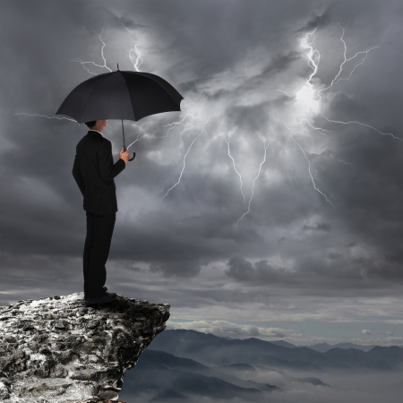 Business Man with an umbrella look rainstorm clouds and lightning over danger precipice on the mountain,  concept for business and insurance
