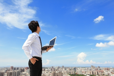 Foto de Young business man using laptop and look to blue sky and cloud with cityscape in the background, business and cloud computing concept - Imagen libre de derechos