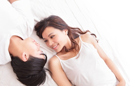 young lovely couple lying in a bed, happy smile looking to each other, top view, asian people