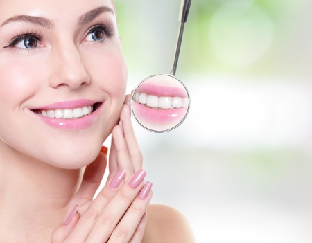 attractive smiling woman face with health teeth close up and a dentist mouth mirror, dental care concept