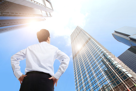 Photo pour happy successful business man outdoors Next to Office Buildings with cityscape and sky, hong kong, asia, asian - image libre de droit